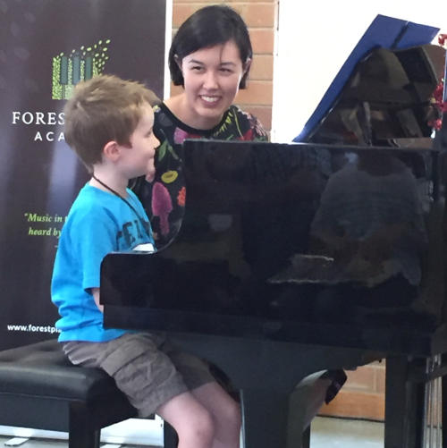 Boy playing piano with his teacher