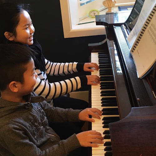 Kids playing on a piano