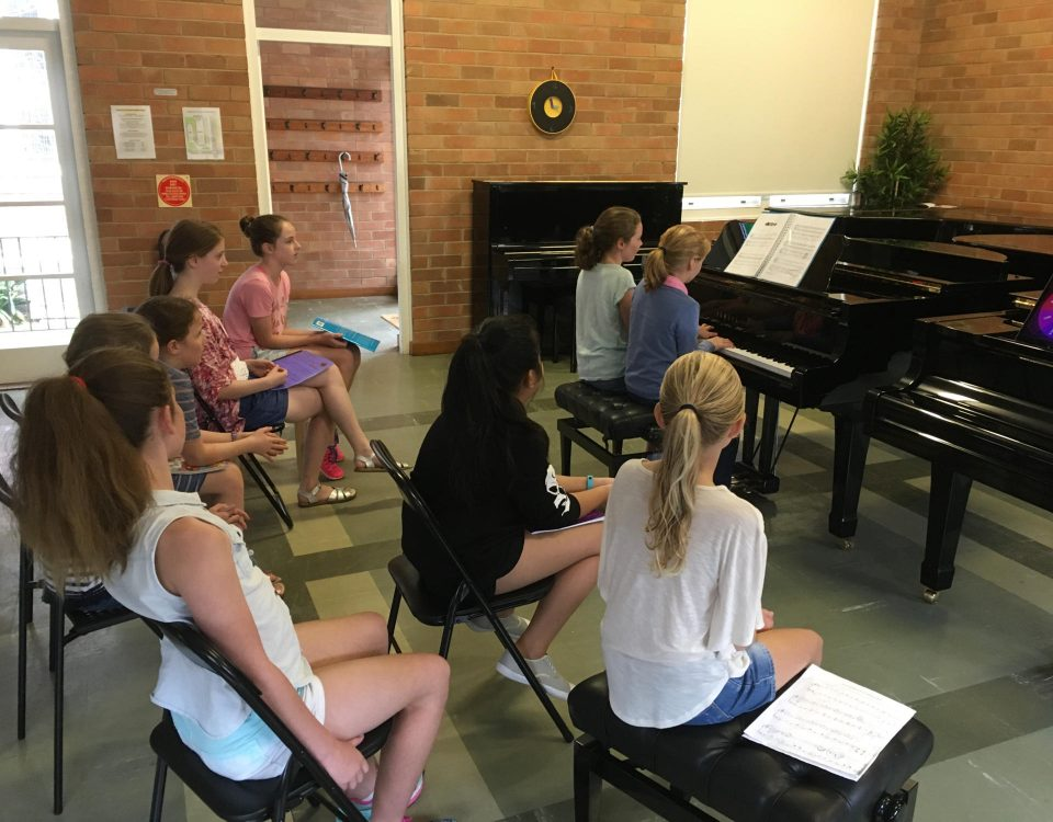 Kids practising piano during a group lesson